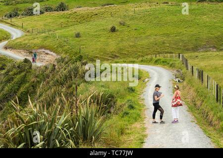 Two women on a walking path at Cape Foulwind, West Coast, South Island, New Zealand. - Stock Photo