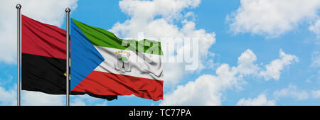 Angola and Equatorial Guinea flag waving in the wind against white cloudy blue sky together. Diplomacy concept, international relations. - Stock Photo