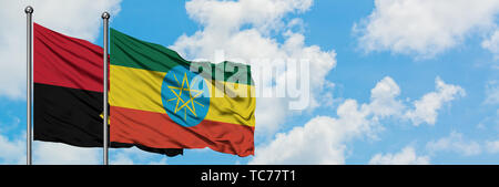 Angola and Ethiopia flag waving in the wind against white cloudy blue sky together. Diplomacy concept, international relations. - Stock Photo