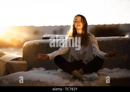 young calm woman meditating on abandoned snowy couch in lotus position, winter time, relaxing, in Cottbus, Brandenburg, Germany Stock Photo