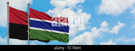 Angola and Gambia flag waving in the wind against white cloudy blue sky together. Diplomacy concept, international relations. - Stock Photo