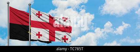 Angola and Georgia flag waving in the wind against white cloudy blue sky together. Diplomacy concept, international relations. - Stock Photo