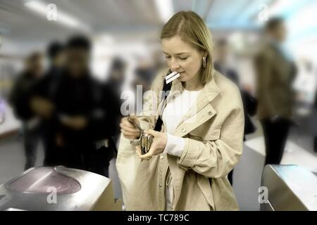 fashionable woman searching for ticket in purse to enter public transport system, metro, in Paris, France. - Stock Photo