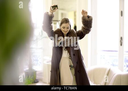 fashionable woman with new stylish designer coat putting hands up, holding phone, in Paris, France. - Stock Photo