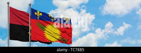 Angola and Guadeloupe flag waving in the wind against white cloudy blue sky together. Diplomacy concept, international relations. - Stock Photo