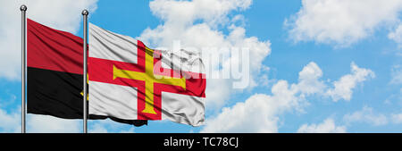 Angola and Guernsey flag waving in the wind against white cloudy blue sky together. Diplomacy concept, international relations. - Stock Photo