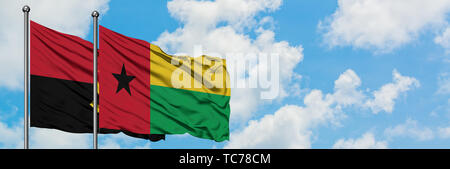 Angola and Guinea Bissau flag waving in the wind against white cloudy blue sky together. Diplomacy concept, international relations. - Stock Photo