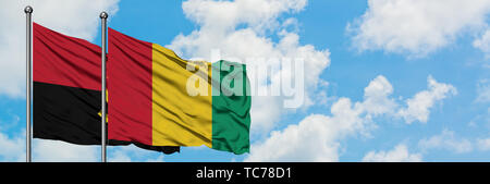 Angola and Guinea flag waving in the wind against white cloudy blue sky together. Diplomacy concept, international relations. - Stock Photo
