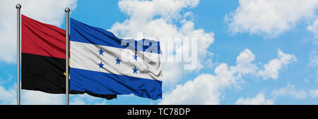 Angola and Honduras flag waving in the wind against white cloudy blue sky together. Diplomacy concept, international relations. - Stock Photo
