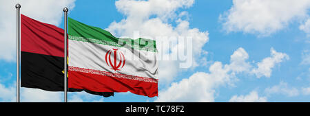 Angola and Iran flag waving in the wind against white cloudy blue sky together. Diplomacy concept, international relations. - Stock Photo