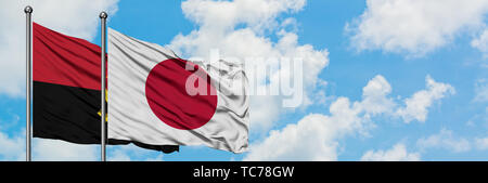 Angola and Japan flag waving in the wind against white cloudy blue sky together. Diplomacy concept, international relations. - Stock Photo