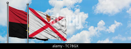 Angola and Jersey flag waving in the wind against white cloudy blue sky together. Diplomacy concept, international relations. - Stock Photo