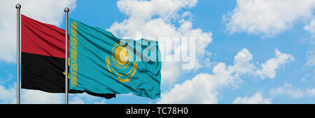 Angola and Kazakhstan flag waving in the wind against white cloudy blue sky together. Diplomacy concept, international relations. - Stock Photo