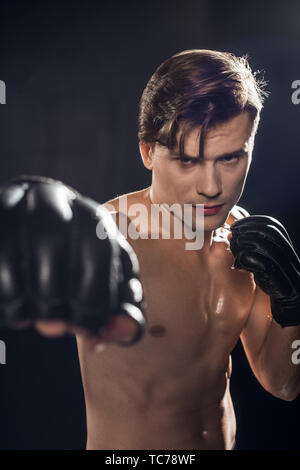 Selective focus of concentrated boxer in boxing gloves training and looking at camera - Stock Photo