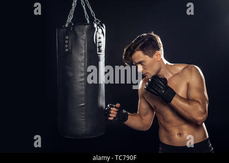 Handsome boxer in boxing gloves training with punching bag on black - Stock Photo