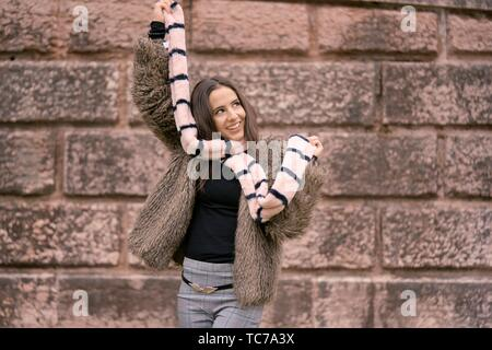 lively woman playing with scarf, in Munich, Germany - Stock Photo