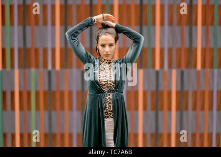 portrait of confident fashionable woman, in front of geometrical line pattern, in Munich, Germany - Stock Photo