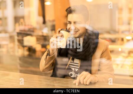 young man behind window drinking coffee from plastic cup in café in Munich, Germany.