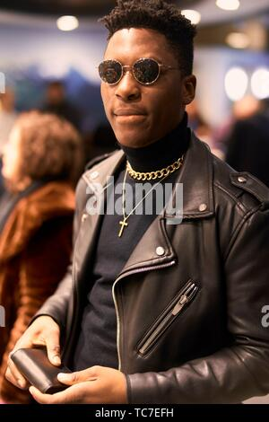 fancy young man holding wallet in hands in city between passersby, African descent, wearing sunglasses, leader jacket, jewellery, Christian cross, - Stock Photo