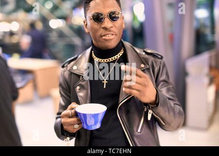 young fancy man holding coffee cup and gesticulating, African descent, in Munich, Germany. - Stock Photo