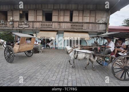 Kalesa horse carriages on historic Calle Crisologo, Vigan, Ilocos Sur, Philippines. - Stock Photo