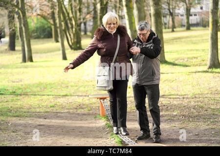 senior man helping senior woman to balance on slackline at playground, old couple, in Cottbus, Brandenburg, Germany. - Stock Photo
