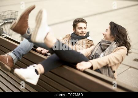 young smiling teenage couple sitting on bench the wrong way round in city, hanging out together, legs up, upside down, in Cottbus, Brandenburg,