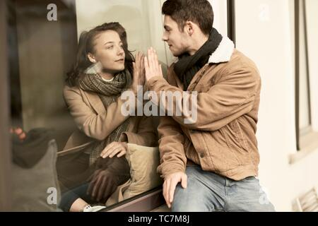 young teenage couple separated by window, trying to touch hands, in Cottbus, Brandenburg, Germany - Stock Photo