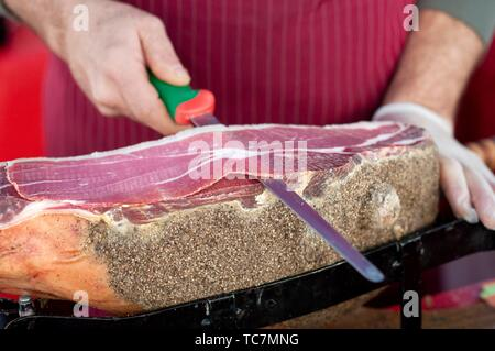 Italy, Umbria, Norcia, Stall Market, Market Stall Trader Carving a Ham.. - Stock Photo