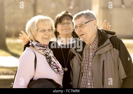 mature woman between senior couple, about to put heads together, in Cottbus, Brandenburg, Germany - Stock Photo