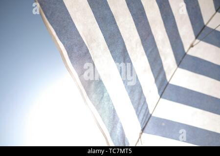 White and blue umbrella under the sun and blu sky - Stock Photo