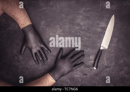Big Knife and Male Hands with Black Latex Gloves on Dark Background - Stock Photo