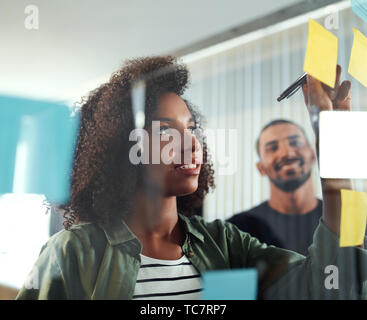 Office colleagues writing business ideas and plans on sticky not - Stock Photo