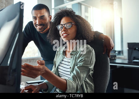Businesswoman showing something to her colleague on computer - Stock Photo