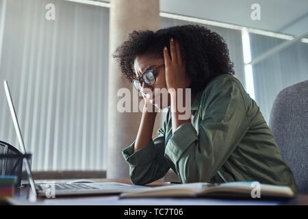Worried young african businesswoman at her workplace - Stock Photo