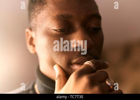 thoughtful young man, hand fondling lips, in Munich, Germany. - Stock Photo