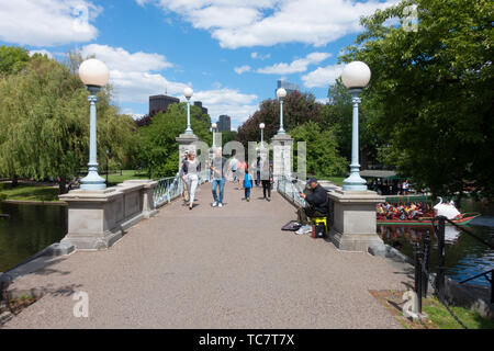Pedestrian walking bridge over the lagoon with swan boat at the Boston Public Garden adjacent to the Common on a beautiful day with people crossing