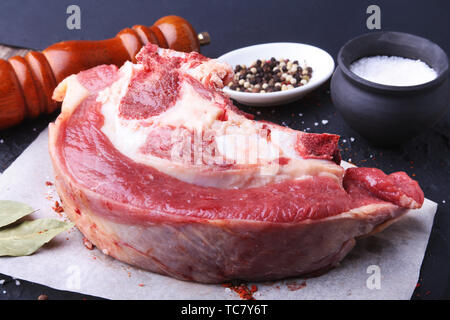 Raw fresh meat, uncooked lamb or beef ribs with pepper, garlic, salt, bay leaves and spices on dark stone background, Ready for cooking. copy space. - Stock Photo