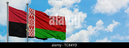 Angola and Belarus flag waving in the wind against white cloudy blue sky together. Diplomacy concept, international relations. - Stock Photo