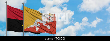 Angola and Bhutan flag waving in the wind against white cloudy blue sky together. Diplomacy concept, international relations. - Stock Photo