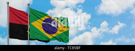 Angola and Brazil flag waving in the wind against white cloudy blue sky together. Diplomacy concept, international relations. - Stock Photo