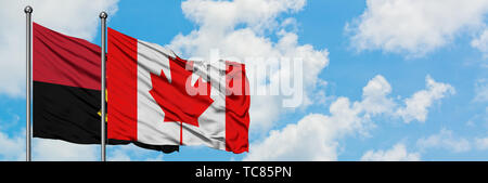 Angola and Canada flag waving in the wind against white cloudy blue sky together. Diplomacy concept, international relations. - Stock Photo