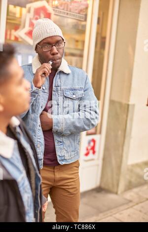 young man using electronic cigarette, in Munich, Germany. - Stock Photo
