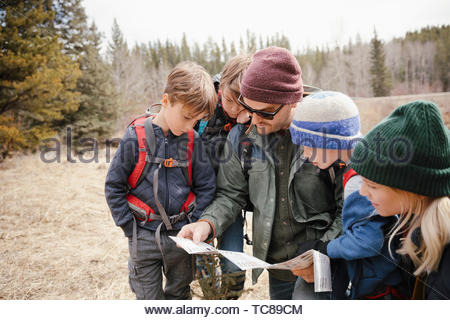 Family with trail map hiking in woods - Stock Photo