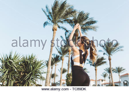 Portrait attractive young sportswoman stretching on palm trees, blue sky background. Sunny morning, workout, motivation, fitness, training, relaxation. Place for text - Stock Photo
