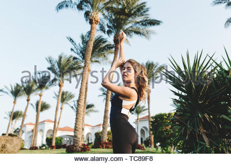 Amazing attractive woman in sportswear stretching hands above on palm trees, blue sky background. Tropical city, looking to camera, outwork, training, healthy lifestyle - Stock Photo