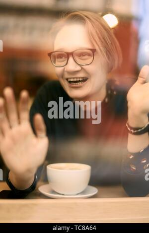 happy woman indoors behind glass window in coffee shop, Munich, Germany. - Stock Photo
