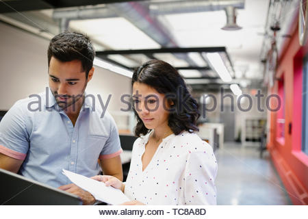 Business people with laptop and paperwork in office - Stock Photo