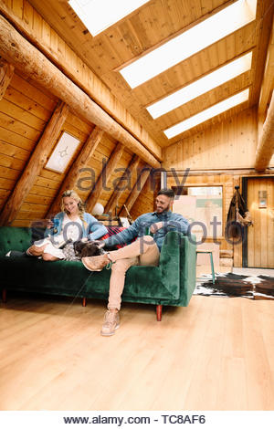 Couple with dog relaxing, reading book on cabin sofa - Stock Photo