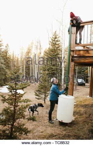 Couple with dog installing rain barrel outside cabin - Stock Photo